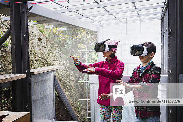 Mixed Race brother and sister using virtual reality goggles on veranda