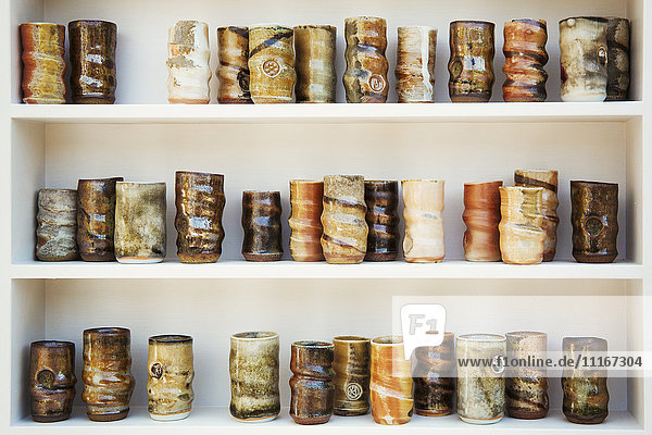 A large number of ceramic jars arranged in rows on shelves. Different firing and glazing techniques  and a variety of natural colours.