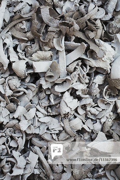 A heap of offcuts,  curls of clay removed in the process of shaping.