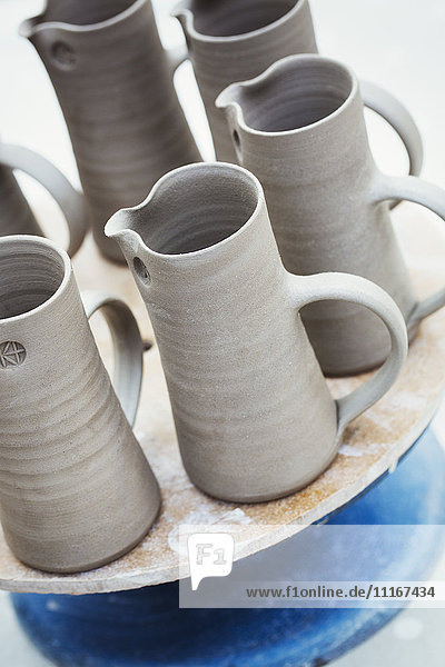 A group of hand thrown jugs with handles and pouring spouts ready for firing.