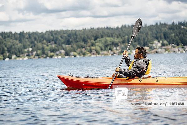 Mixed Race man paddling kayak