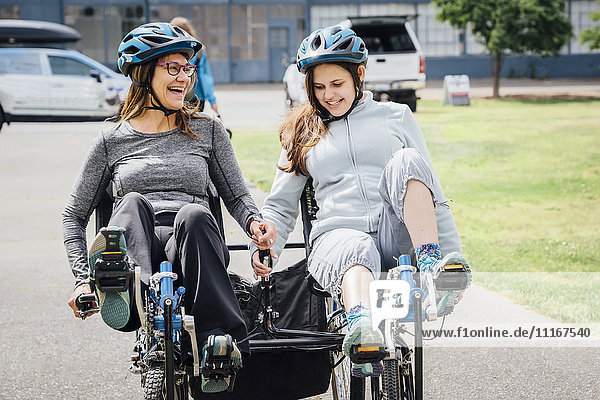 Caucasian mother and daughter riding tandem bicycle