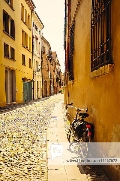 Bicycle leaning in building near street  Bologna  Emilia-Romagna  Italy