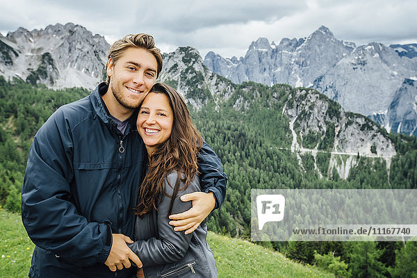 Caucasian couple hugging neat mountain range  Tarvisio  Vienna  Austria