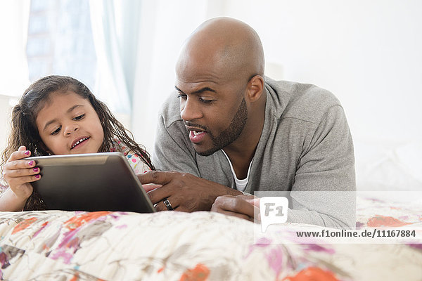 Father and daughter using digital tablet on bed