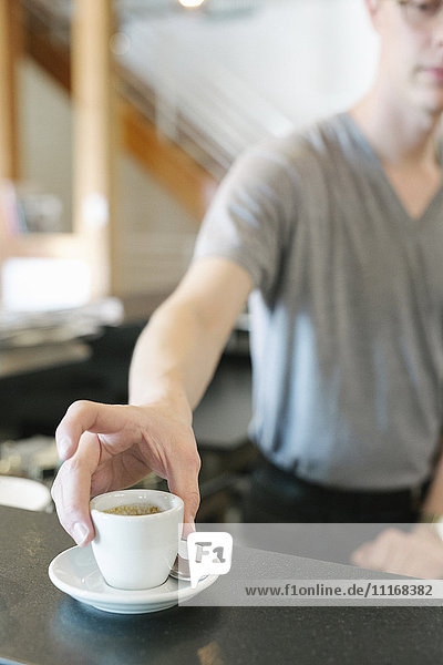 Man standing at a counter in a coffee shop  reaching for a cup of espresso coffee.