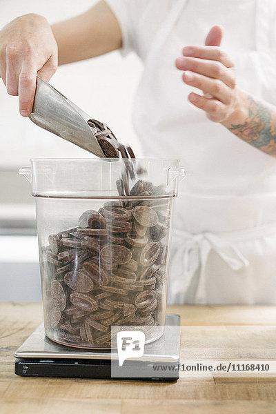 Nahaufnahme einer Frau mit weißer Schürze  die an einem Arbeitstresen in einer Bäckerei steht und Schokolade wiegt. Nahaufnahme einer Frau mit weißer Schürze, die an einem Arbeitstresen in einer Bäckerei steht und Schokolade wiegt.