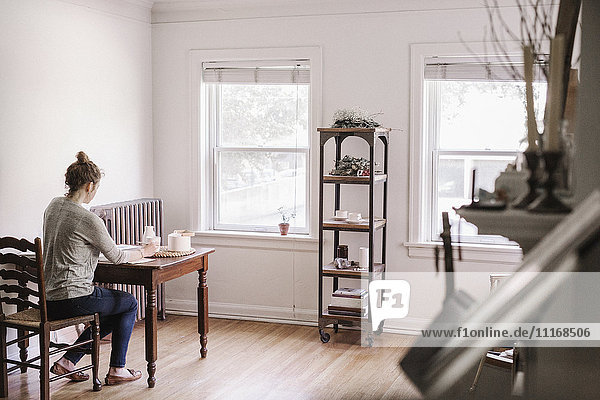 Woman sitting at a table in her apartment  writing in a diary  morning routine.