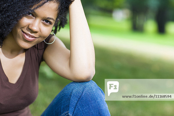 Smiling Mixed Race woman sitting in park