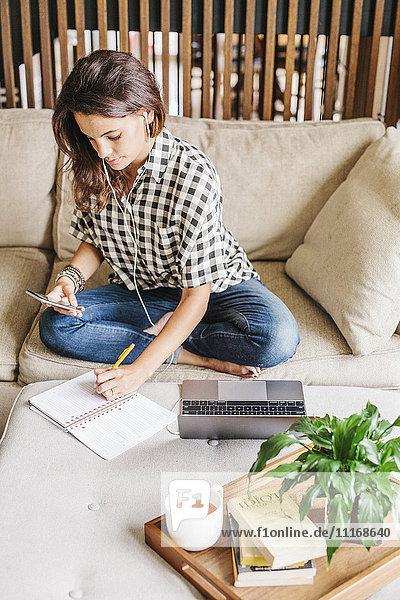 Frau mit langen braunen Haaren sitzt auf einem Sofa mit Laptop und Notebook und arbeitet.