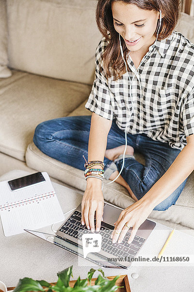 Woman with long brown hair sitting on a sofa with a laptop computer and notebook  working.