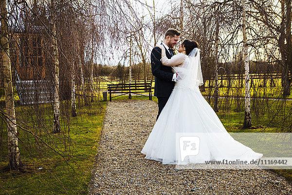 Braut und Bräutigam Hand in Hand  an ihrem Hochzeitstag  in einem Garten.