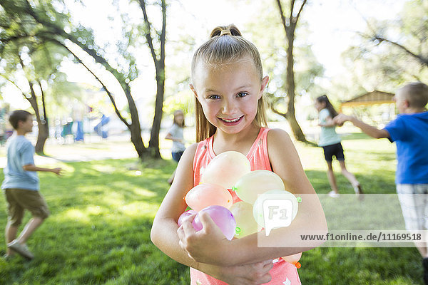 Caucasian girl holding water balloons