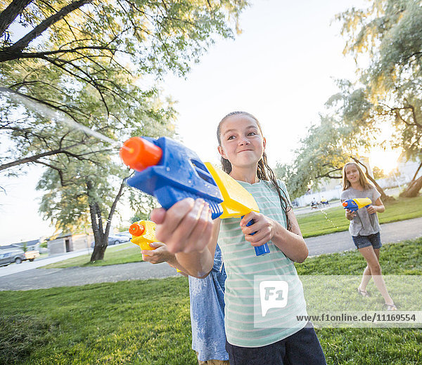 Caucasian girls playing with squirt guns