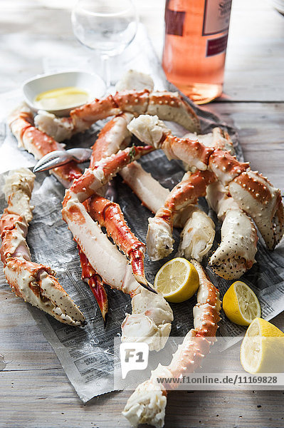 Crab legs and lemon slices on newspaper