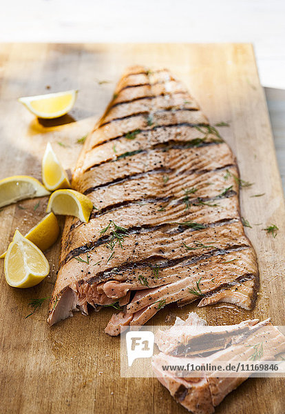 Salmon on cutting board with lemon wedges