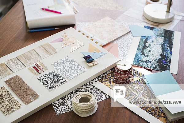 Craft materials  fabric and paper  patterns and a notebook and tablet.