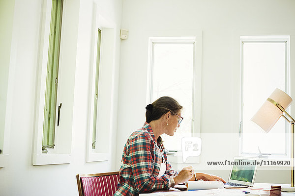 Eine Frau  die an ihrem Schreibtisch sitzt und ein Collagebild erstellt.