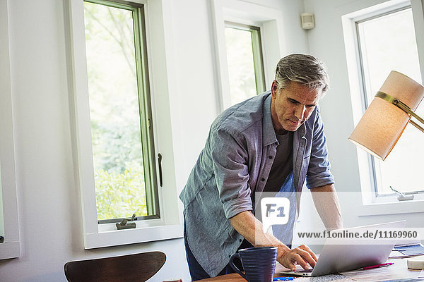 A man at home using a laptop on a desk.