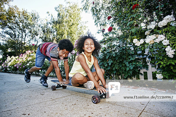 Mixed Race boy pushing sister on skateboard on sidewalk