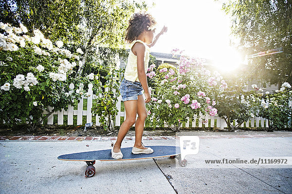 Mixed Race girl skateboarding on sidewalk