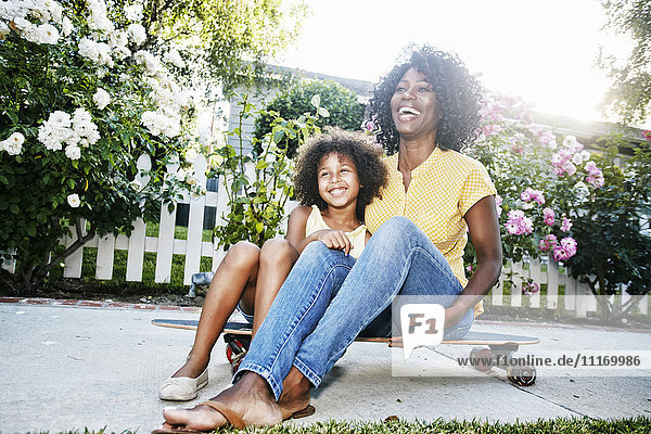 Smiling mother and daughter sitting on skateboard