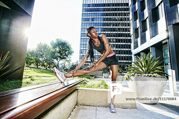 Serious Black woman stretching leg on urban bench