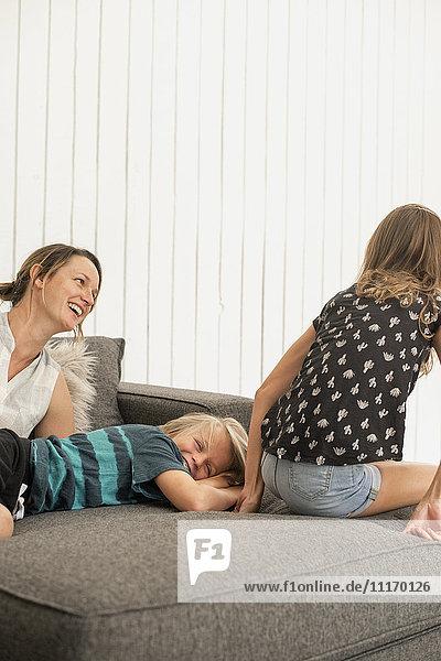Mutter  Sohn und Tochter auf einem Sofa.