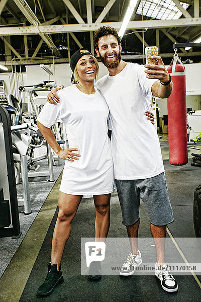 Mixed Race man couple posing for cell phone selfie in gymnasium