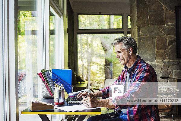 Ein Mann  der zu Hause an einem Schreibtisch sitzt und an einem Laptop-Computer arbeitet.