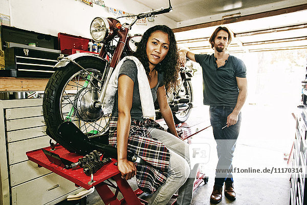Serious man and woman posing with motorcycle in garage