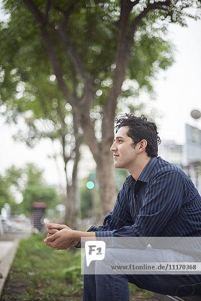 Smiling Hispanic man sitting on bench