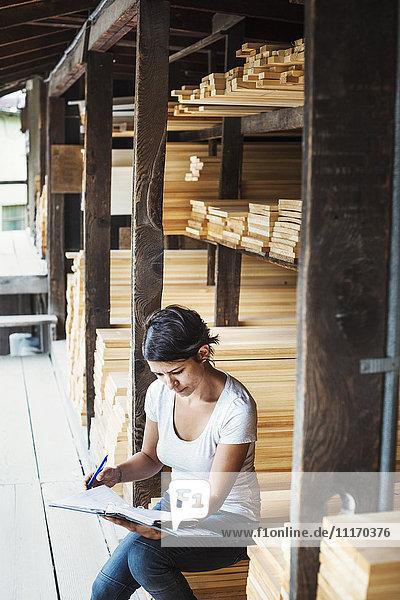 Woman sitting in a lumber yard  holding a folder.