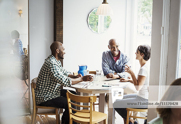 Two men and a woman sitting at a table in a cafe  having lunch.
