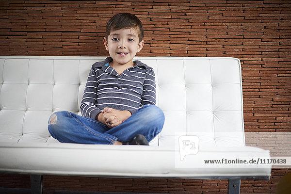 Hispanic boy sitting cross-legged on sofa