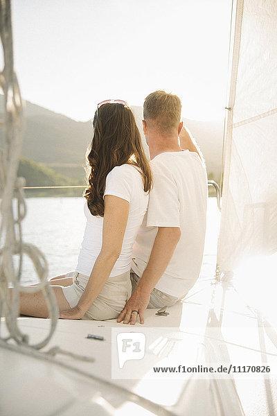 Frau und junges Mädchen sitzen auf einem Segelboot.