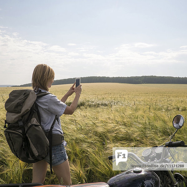 Caucasian woman standing in field near motorcycle using cell phone