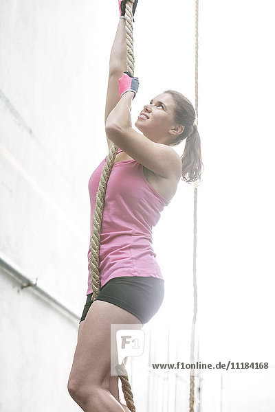 Dedicated woman climbing rope in crossfit gym