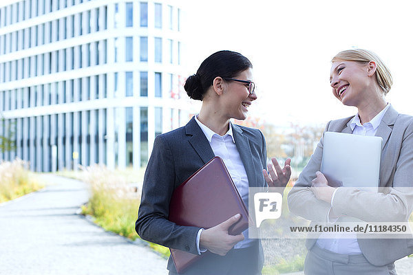 Cheerful businesswomen conversing while holding folder and laptop outside office building