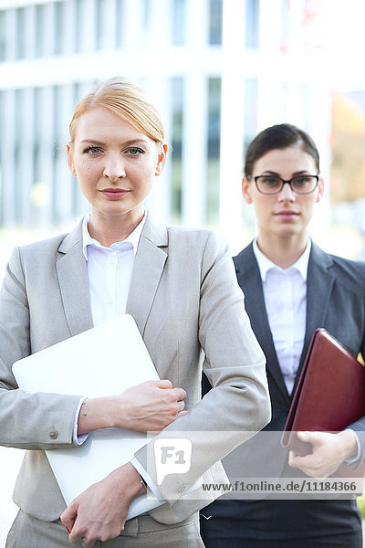 Portrait of confident businesswoman holding laptop with colleague in background