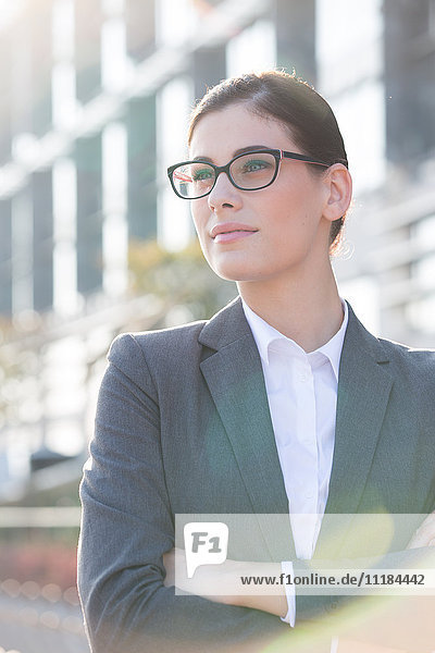 Thoughtful businesswoman standing arms crossed outdoors