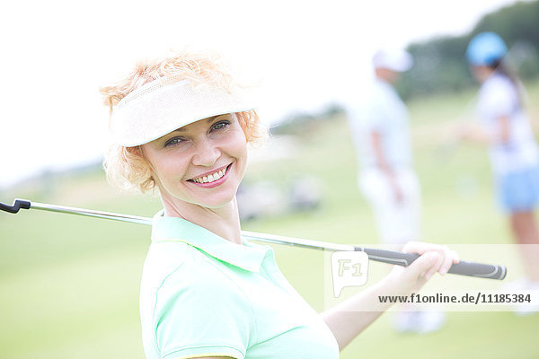 Portrait of happy female golfer holding golf club