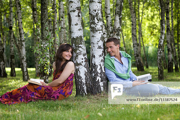 Young couple holding books in park by tree trunk  looking at each other