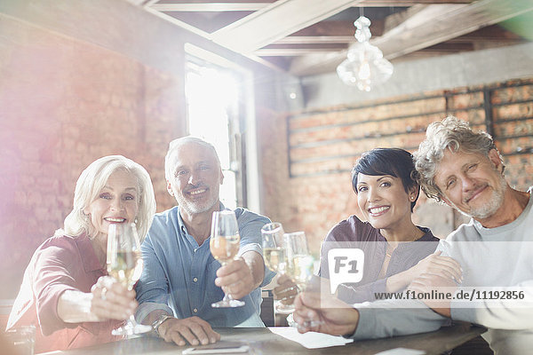Portrait smiling couples toasting white wine glasses at restaurant table