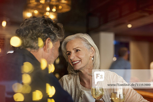 Affectionate smiling senior couple drinking white wine in bar