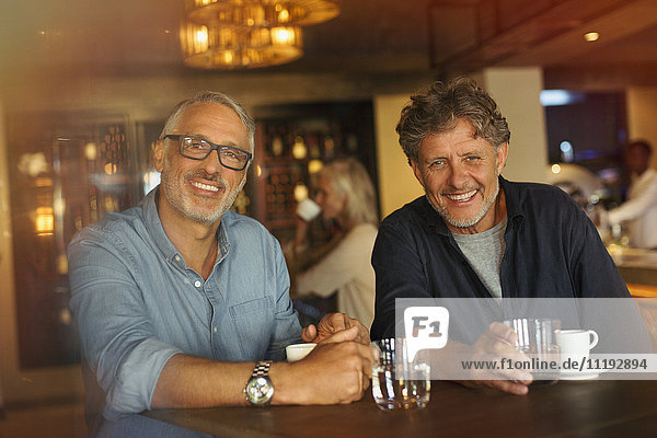 Portrait smiling men drinking coffee and water at restaurant table