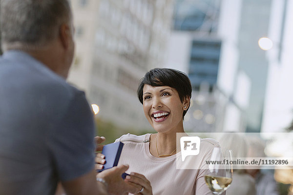 Smiling woman receiving gift from husband at urban sidewalk cafe