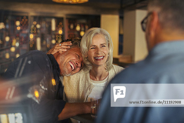 Affectionate senior couple laughing and hugging in bar