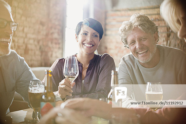 Laughing couples drinking white wine and beer at restaurant table