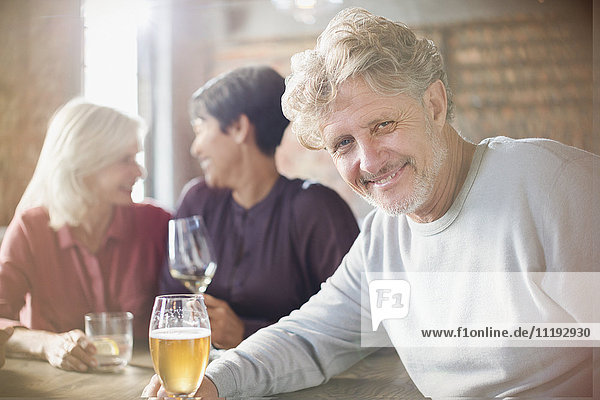 Portrait smiling senior man drinking beer dining with friends at restaurant table